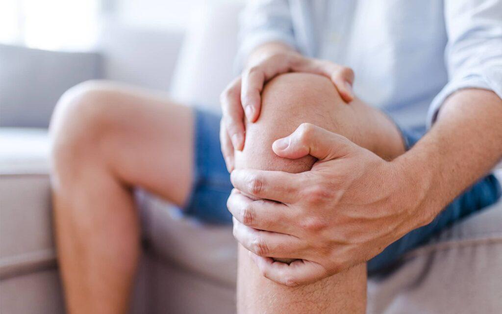 Homme se tenant le genou en signe de douleur