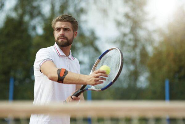 Tennisman prêt à servir et portant une attelle anti-épicondylite