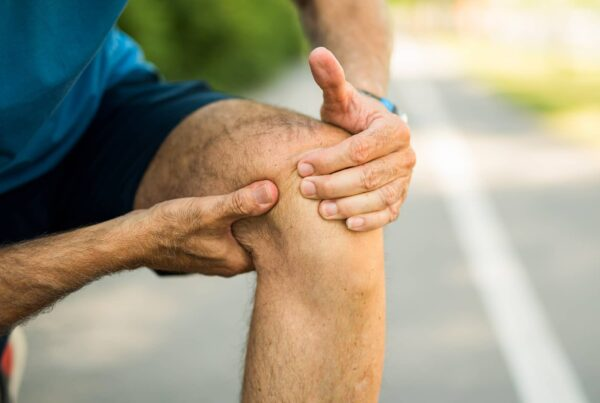 Homme en tenue de sport, se tenant le genou suite à une douleur d'arthrose