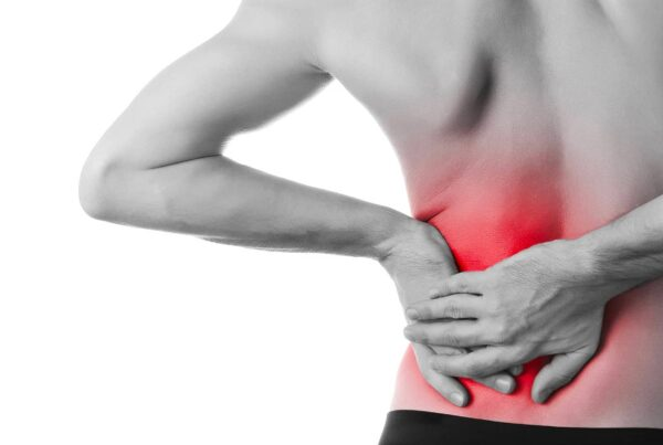 Buste d'homme de dos avec mains posées sur la zone lombaire pour illustrer la douleur de la hernie discale