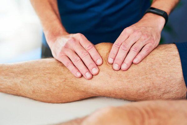Genou d'un homme se faisant masser par un kinésithérapeute dans le cadre d'une instabilité rotulienne
