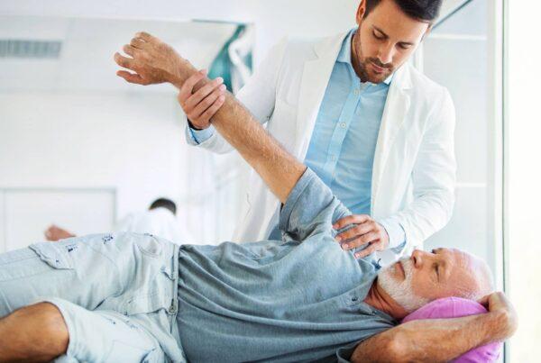 Homme se faisant manipuler l'épaule pour une luxation