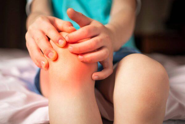 Jeune garçon se tenant le genou en signe de douleur – Maladie d'Osgood-Schlatter