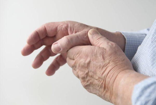 Mains d'un homme âgé se tenant le pouce en signe de rhizarthrose
