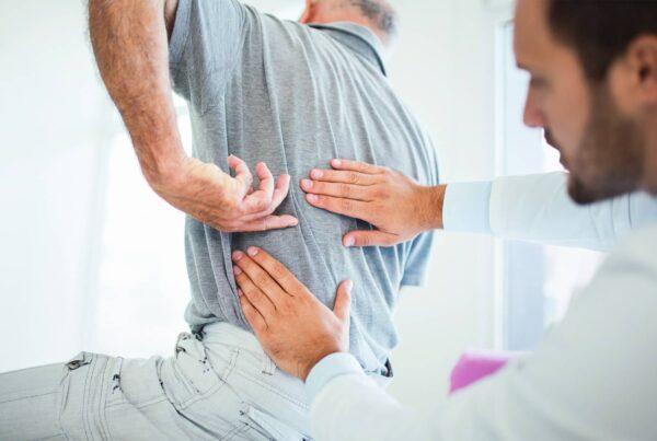 Homme se faisant manipuler le dos par un professionnel de santé dans le cadre d'une sciatique