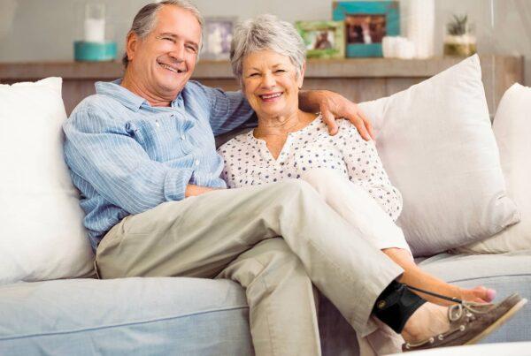 Couple âgé dans son canapé avec homme portant un releveur de pied