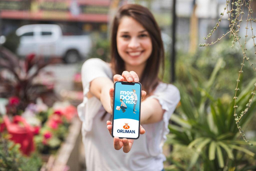 Photo d'une femme montrant un smartphone avec l'application mobile mon dos & moi - orliman