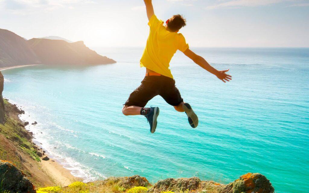 Photo d'un homme sautant face à la mer et portant une attelle de cheville Orliman