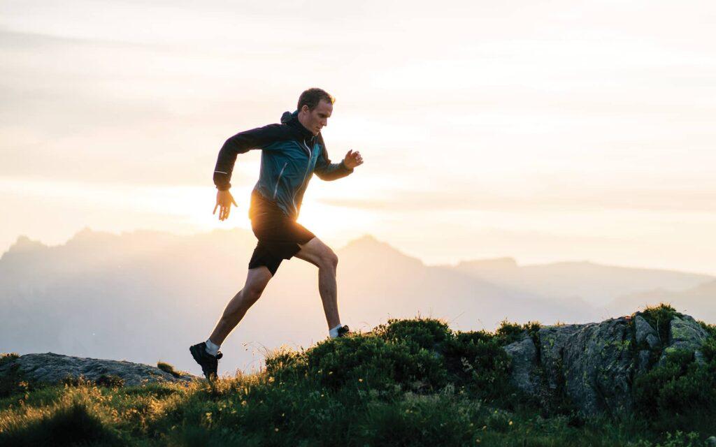 homme sportif faisant un jogging sur fond de paysage de montagne