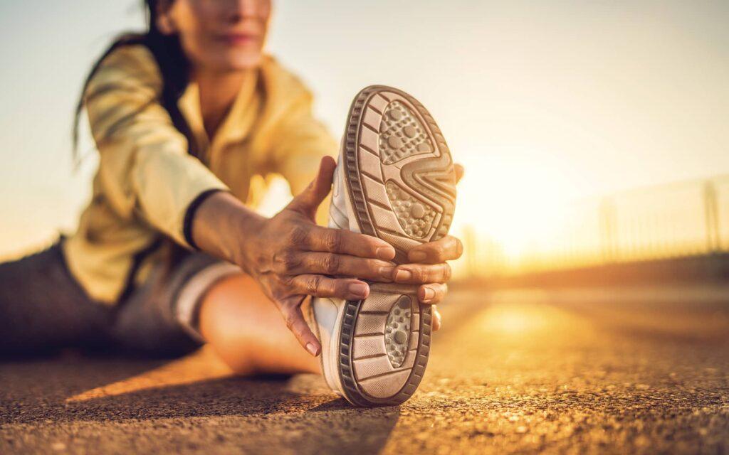 Femme sportive assise au sol s'étirant le pied